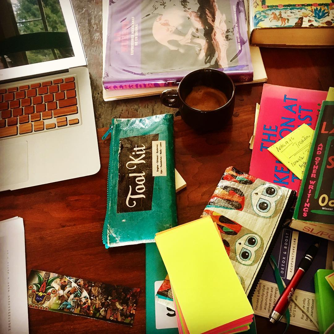 Messy writing desk cover in books and a laptop