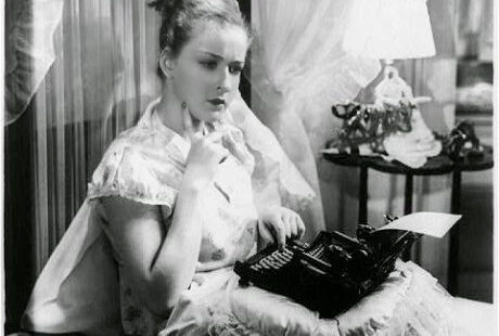 women in bed writing on typewriter